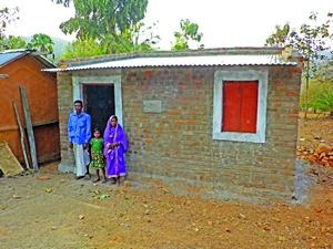 Христианская семья в штате Орисса, Индия, перед своим новым домом, построенным Фондом Варнава