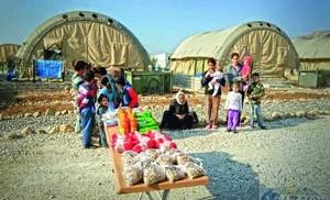 Семьи собрались у своих палаток в ожидании раздачи продовольственной помощи