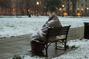 A homeless man sits covered in snow
